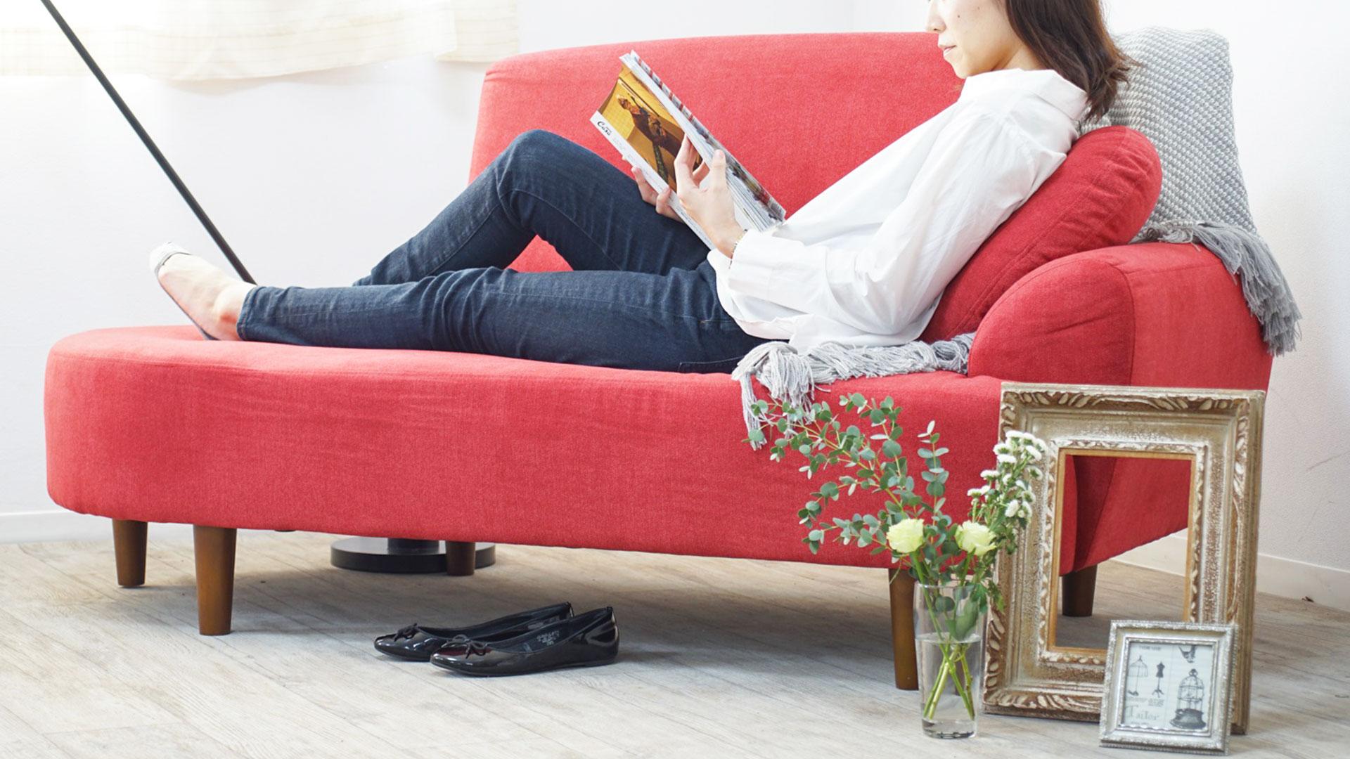 リビンズの2人掛けソファ「マチルダ」の脚を伸ばしてくつろいでる画像